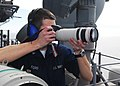 US Navy 101122-N-2218S-003 Intelligence Specialist 3rd Class Scottie Ford photographs a contact off the starboard side of the amphibious assault sh.jpg