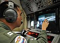 US Navy 110322-N-MU720-009 Lt. Jae Kim, from San Diego, assigned to Patrol Squadron (VP) 4, reviews aerial images of northeast Japan aboard a P-3 a.jpg