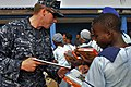 US Navy 120216-N-IZ292-060 Boatswain's Mate Seaman Joshua Maurer, assigned to the guided-missile frigate USS Simpson (FFG 56), hands books to school.jpg