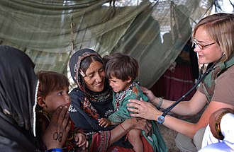 Kochi people - US army medic vaccinating Kochi children, Gardez, 2003.
