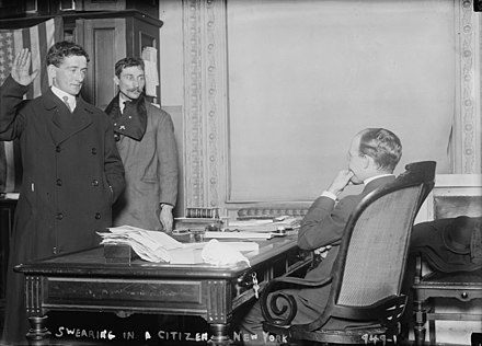 A man taking the required citizenship oath of allegiance in front of U.S. government officials in New York City (1910). Usnaturalization.jpg