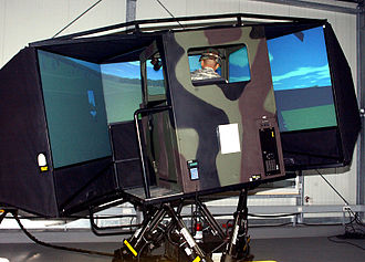 Simulation - A soldier tests out a heavy-wheeled-vehicle driver simulator.