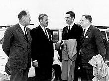 Quatro homens em ternos são ao ar livre, falando um com o outro na frente de um grande automóvel branco.