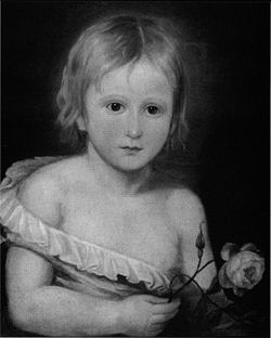 Black-and-white half-length portrait of a toddler, wearing a small shirt that is falling off of his body, revealing half of his chest. He has short blonde hair and is holding a rose.
