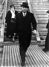 A middle-aged man in a dark coat and top-hat strides confidently along a boardwalk at the base of a set of steps. A well-dressed woman is on the steps behind him, while a third person, a man, approaches the steps.