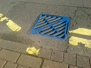 Water pollution - Blue drain and yellow fish symbol used by the UK Environment Agency to raise awareness of the ecological impacts of contaminating surface drainage