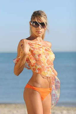 Young woman in orange Tanga-Bikini on the beach