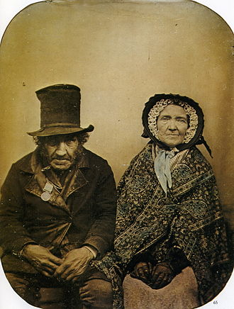 "Collodion process - ""A Veteran with his Wife"", taken by an anonymous photographer, shows a British veteran of the Napoleonic era Peninsular Wars. It is a hand-tinted ambrotype using the set collodion positive process, made circa 1860."