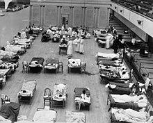 dutzende Betten mit liegenden oder sitzenden Grippeerkrankten in einem Hörsaal in Oakland, betreut von mehreren Krankenschwestern und Ärzten mit Masken