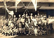 Une famille se réunit autour d'un jeune garçon en uniforme militaire, entouré par des bannières et des drapeaux.  Certains des enfants tiennent aussi des drapeaux.