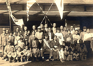 Flag of Japan - 1930s photo of a military enrollment. The Hinomaru is displayed on the house and held by several children.