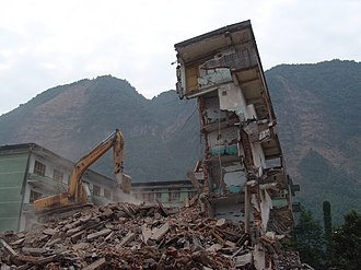 2008 Sichuan earthquake - A collapsed residential block in Wenchuan being bulldozed in the aftermath of the earthquake; exposed mountain faces can be seen in the background.