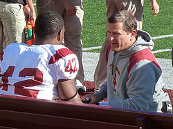 Candid photograph of Berry wearing a hooded sweatshirt with a USC logo and kneeling on a football sideline and speaking with a player seated on a bench