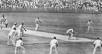 On a cricket field, a batsman ducks under the ball, watched by the man who had bowled the ball, another batsman and an umpire. There are a ring of men standing fielding next to the batsman. Everyone is wearing white shirts and trousers, with the fielders in caps. A large crowd is behind a fence in the background.