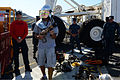 A guest touring the aircraft carrier USS Ronald Reagan (CVN 76) dons part of a firefighting ensemble 130921-N-TO979-025.jpg