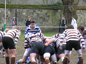 Winchester College football - College Xs. A hot between OTH (brown and white) and College (blue and white) on Meads in 2006. A man wearing the Commoners shirt (red and white) stands near Worms (far left).