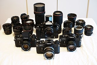 Canon F-1 - Four Canon F-1 cameras displayed alongside an assortment of FD mount lenses
