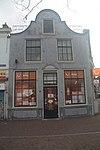 foto van Huis met eenvoudige gepleisterde brede halsgevel met enig smeedwerk
