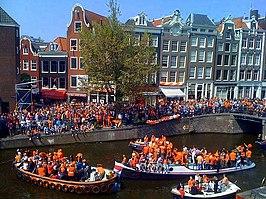 De Amsterdamse grachten kleuren oranje met feestvierders en bootjes op de Prinsengracht; 30 april 2010.