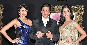 A man in a suit is interlocking arms with two women. The woman on the left is wearing a blue one-shouldered gown with her hair up, while the woman on the right is wearing a gold sari (South Asian attire) with her hair down.