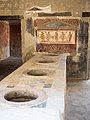 Bathroom with toilets and wall art in Pompeii, 2016.jpg