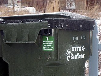 Bear danger - Bear-resistant garbage can. The label gives instructions on how to open.