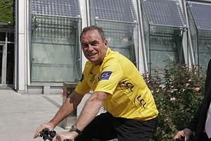 Photographie d'un homme vêtu d'un maillot jaune, qui roule sur un vélo