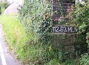Chain (unit) - Location designator painted on a British railway bridge, showing 112 miles and 63 chains; photograph taken August 2007