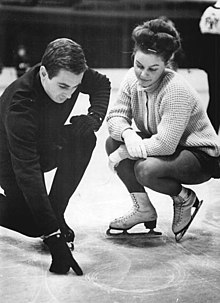 Man on the left and woman on the right crouching on a piece of ice on a rink, the man tracing a figure on the ice with his thumb