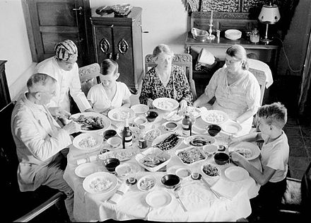 Dutch family enjoying a large Rijsttafel dinner, 1936. COLLECTIE TROPENMUSEUM De familie C.H. Japing met tante Jet en oom Jan Breeman aan de rijsttafel Bandoeng TMnr 10030167.jpg