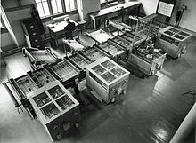 Looking down from above at a room at an intricate mechanical device which fills the room. In the background, a man sits at a desk next to a filing cabinet. [13]