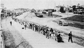 Pleasant Point, New Zealand - Procession for Bowling Carnival circa 1938, led by Mr H. Christie and the two Carnival Queens, D. Chapman and D. Murphy