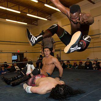 Leg drop -  Chief Ade (right) executes a leg drop