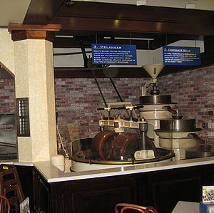 Chocolate liquor - A chocolate mill (right) grinds and heats cocoa beans into chocolate liquor. A melanger (left) mixes milk, sugar, and other ingredients into the liquor.