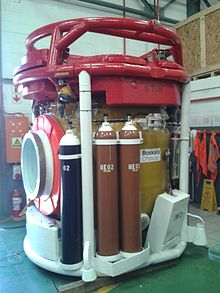 Exterior view of a closed bell, showing the side door to the left, with a 50-litre oxygen cylinder and two 50-litre heliox cylinders mounted to the frame to the side of the door.