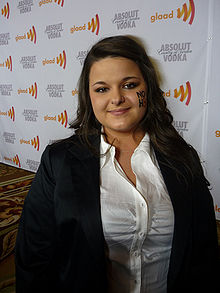 "18-year-old Caucasoid female with a left-nostril piercing and the letters ""NO H8"" painted on her left cheek is wearing a white shirt and black coat and standing in front of a banner advertising the ""GLAAD awards"" and ""Absolut Vodka""."