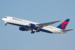 A side/underneath view of a 767-300ER in Delta Air Lines' white, blue and red color while in-flight
