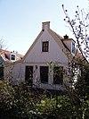 foto van Houten huis met aangebouwde zijbeuk aan de linkerzijde en een puntvormig voorschot
