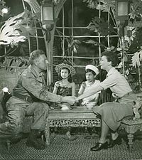 Emile and Nellie grasp hands as Emile's two children look on.