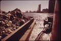 GARBAGE IS TOWED DOWN THE EAST RIVER TO STATEN ISLAND LANDFILL, MANHATTAN IN BACKGROUND - NARA - 549817.tif