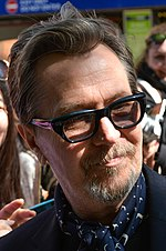 Photo of the 2018 recipient of the Best Actor award: Gary Oldman—a white male from England pictured in 2014 at 56 years of age, with brown hair brushed up and back, a salt-and-pepper goatee, wearing glasses and a dark suit jacket blue neck scarf.