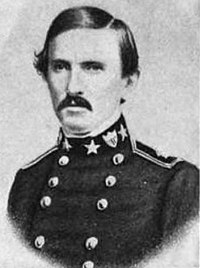 A man in his early forties with short black hair and a mustache. He is wearing a black military coat with two rows of buttons down the front and various military insignia on the collar.