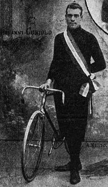 A man standing while holding a bike upright.