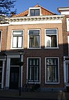 foto van Huis met eenvoudige gevel onder zeer rijk gesneden lijst