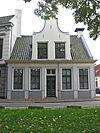foto van Witgepleisterd hoekpand met Vlaamse top