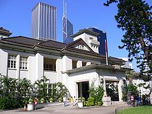 A two-storey neo-classical building showing Japanese architectural influences, with a central two-storey tower. In the foreground is a garden and tennis court and in the background are skyscrapers.