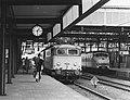 HUA-171410-Afbeelding van de electrische locomotief nr. 1124 (serie 1100) van de N.S. met een internationale trein langs het tweede perron van het N.S.-station Leiden te Leiden.jpg