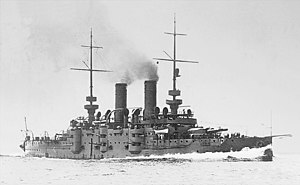 A small grey battleship traveling at full speed with dark smoke billowing out of its two funnels.