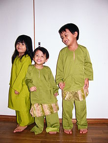 A Malay girl and two Malay boys dressed in green traditional clothing
