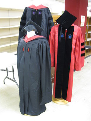 Academic regalia of Harvard University - Three examples of Harvard regalia.  Clockwise from top, these are for a Law School professional doctorate, a Graduate School of Arts and Sciences Ph.D., and a Divinity School master's degree.  The color of the crows-foot lapel emblem represents the school granting the degree.  Note that the Law School gown is black, since it is for a professional doctorate, while the Ph.D. gown is crimson.